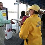 OAKLAND, CA - OCTOBER 18:  Gilda Tablizo (R) passes out schedule information to commuters as they board the San Francisco Bay Ferry on the first day of the Bay Area Rapid Transit (BART) strike on October 18, 2013 in Oakland, California.  For the second time this year, BART workers have gone on strike after contract negotiations between BART management and the transit agency's two largest unions fell apart on Thursday afternoon. Management and unions agreed on the financial specifics of the contract but differed on workplace safety rules.  (Photo by Justin Sullivan/Getty Images)