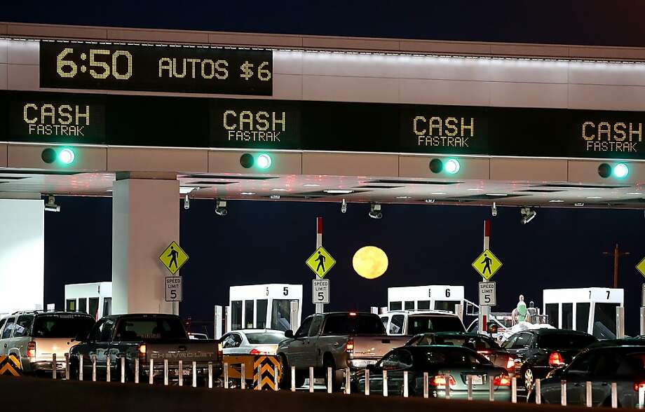 In this file photo, the moon sets as traffic backs up at the San Francisco-Oakland Bay Bridge toll plaza while commuters make their way into San Francisco.  Photo: Justin Sullivan, Getty Images
