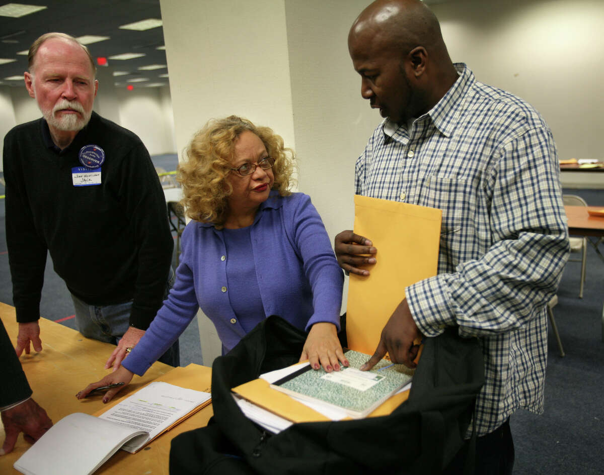 From left; Volunteer Jack Wentland of Glastonbury looks on as Bridgeport Democratic Registrar of Voters Santa Ayala and James Mullen of Bridgeport open a bag of ballots during the election recount at the City Hall Annex in Bridgeport on Tuesday, November 30, 2010.