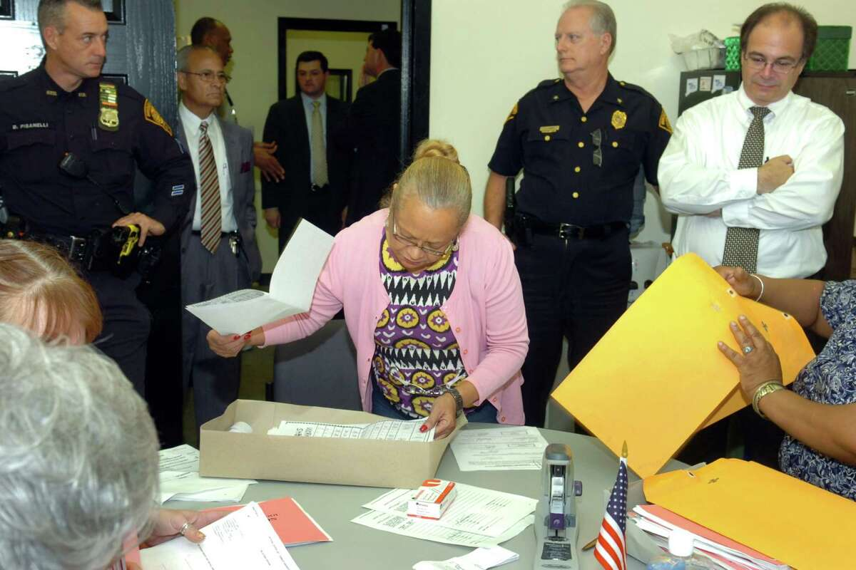 Deputy Chief James Honis stands behind Democratic registrar of voters Santa Ayala as she begins the process of verifying the moderator reports from each of Bridgeport's 25 voting precincts Nov. 4th, 2010.