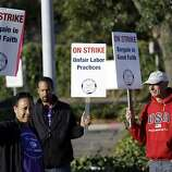 Striking BART workers picket on Friday, Oct. 18, 2013, in Oakland, Calif. Commuters in the San Francisco Bay Area got up before dawn on Friday and endured heavy traffic on roadways, as workers for the region's largest transit system walked off the job for the second time in four months.(AP Photo/Marcio Jose Sanchez)