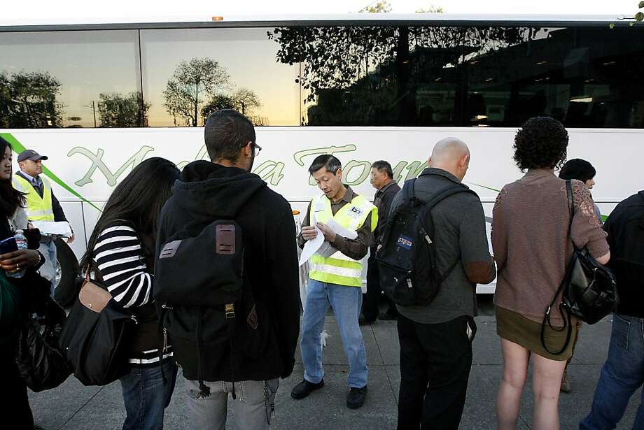 BART Project Manager John Gee, center, hands out tickets and information to passengers boarding transbay busses at the West oakland station in Oakland, CA Friday, October 18, 2013.