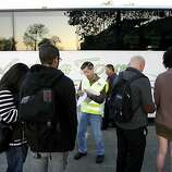BART Project Manager John Gee, center, hands out tickets and information to passengers boarding transbay busses at the West oakland station in Oakland, CA Friday, October 18, 2013. Bay Area Transit workers went on strike shutting down train service after BART management and union leaders with Bay the Amalgamated Transit Union Local 1555 and the SEIU Local 1021failed to reach a contract agreement.