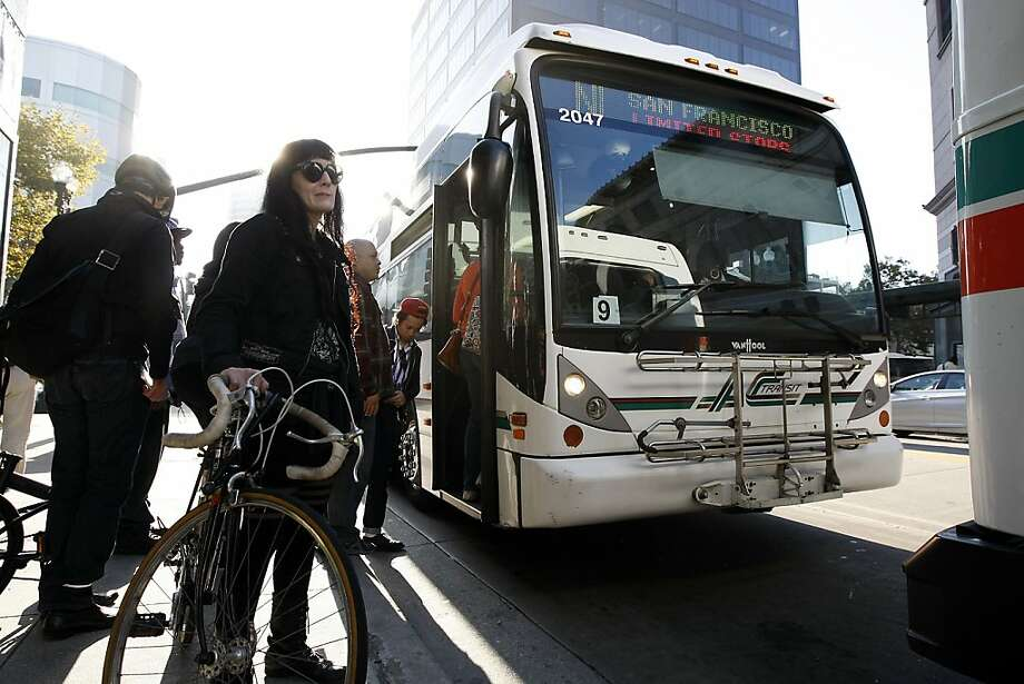 Reah DeCaro of Oakland waits to put her bike on a Transbay AC Transit buss as she heads to San Francisco from downtown Oakland, CA Friday, October 18, 2013. Bay Area Transit workers went on strike shutting down train service after BART management and union leaders with Bay the Amalgamated Transit Union Local 1555 and the SEIU Local 1021failed to reach a contract agreement. Photo: Michael Short, The Chronicle