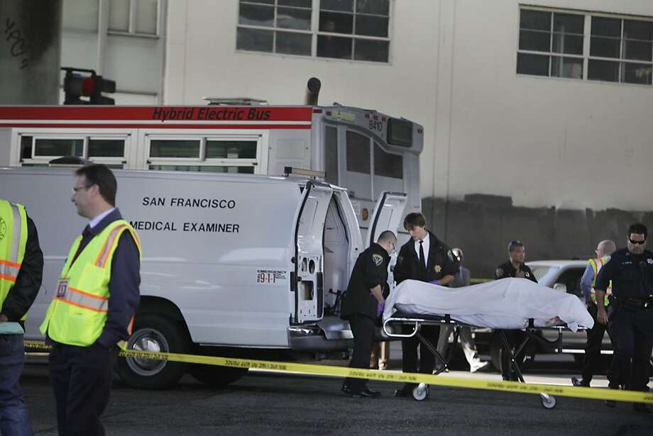 The body of a bicyclist who was killed in a collision with a Muni bus is removed from the scene. Photo: Lea Suzuki, The Chronicle