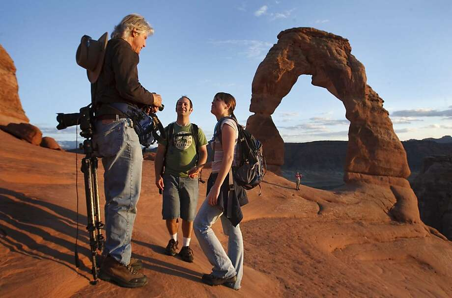 Mind taking our picture, Mr. Giant?Danny and Kelsie Johnson ask Dan Caldemeyer to snap their portrait at the newly reopened Arches National Park in Utah. Photo: Leah Hogsten, Associated Press