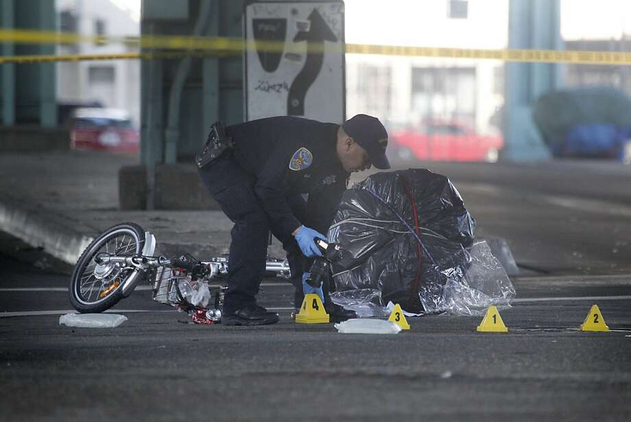 An SFPD officer takes photos while working at the scene where a bicyclist was killed Friday morning in a collision with a Muni bus on Friday, October 18, 2013 in San Francisco, Calif. Photo: Lea Suzuki, The Chronicle