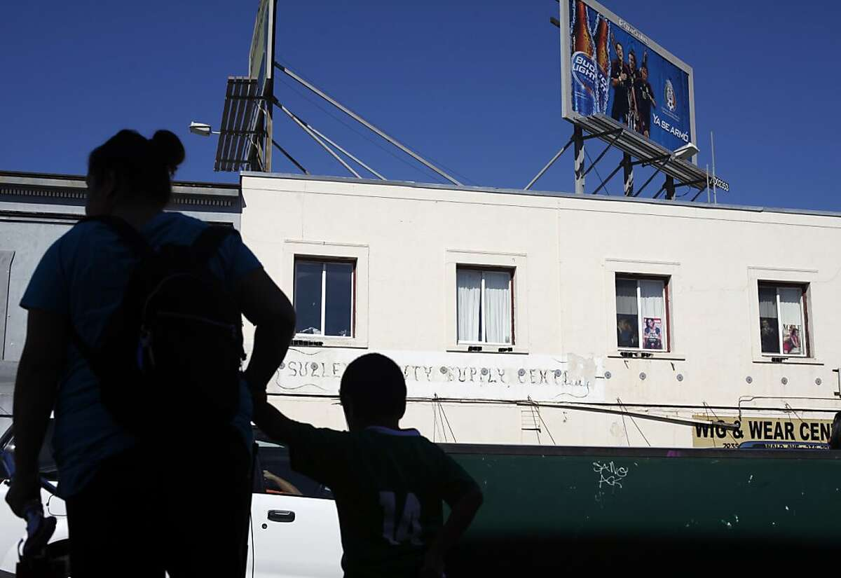 A mother and son wait for the bus at the corner of 23rd and MacDonald, Thursday October 17, 2013, in Richmond, Calif. Richmond City Council have passed a ban on alcohol billboards within 1,000 feet of schools and parks.