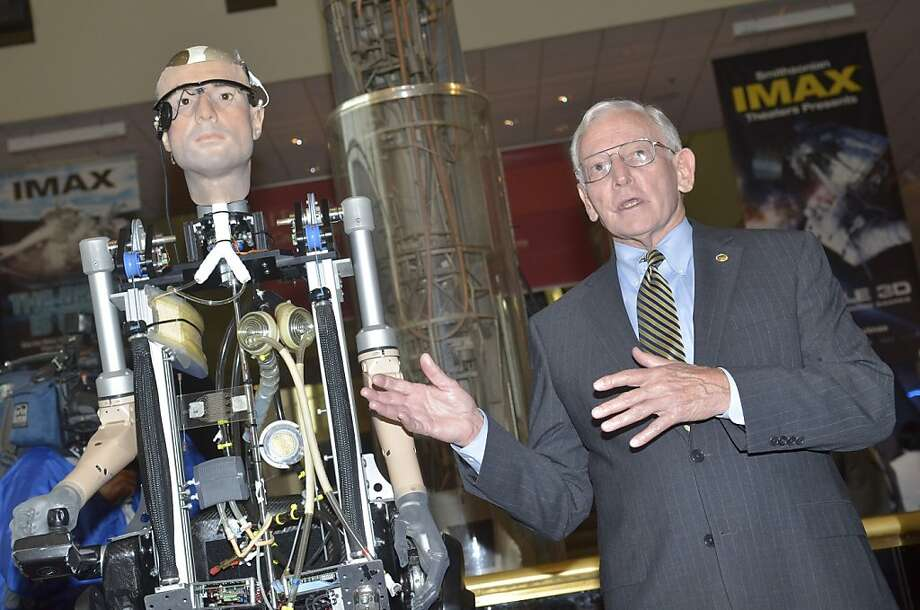 "I'd like to introduce you to the man who will one day have your job: Jack Daily, director of the Smithsonian National Air and Space Museum, unveils the ""Incredible Bionic Man"" at the museum in Washington. The robot cost $1 million and was made from 28 artificial body parts on loan from biomedical innovators. They include a pancreas, lungs, spleen and circulatory system, with most of the parts early prototypes. Photo: Kris Connor, Getty Images For Showtime"