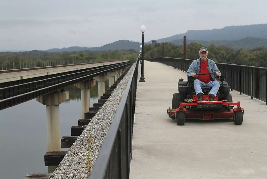 A man in search of lawns: Raymond Pendergrass rides his mower over the Tennessee River in Bridgeport, Ala. The former railroad bridge was converted to a pedestrian walkway. Photo: Maura Friedman, Associated Press