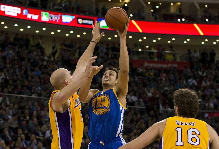 Andrew Bogut of the Golden State Warriors, center, shoots over Chris Kaman of the LA Lakers during their NBA Global Game at the Wukesong Stadium in Beijing Tuesday, Oct. 15, 2013. The Warriors defeated Lakers 100-95. (AP Photo/Andy Wong) Photo: Andy Wong, Associated Press