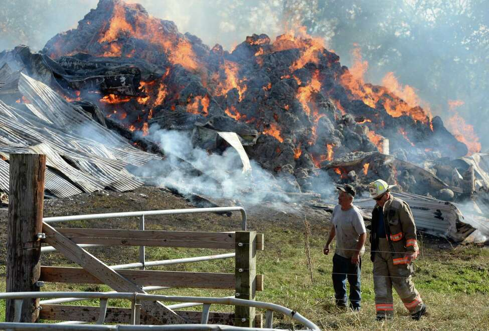 Farm owner Paul Peter, left, walks from the blaze with Rensselaer County Deputy Fire Coordinator Bill Gummer at the Peter Farm Friday afternoon, Oct. 18, 2013, in Castleton-on-Hudson, N.Y. Fire officials reported that as many as twenty young cows were lost in the fire. (Skip Dickstein/Times Union)