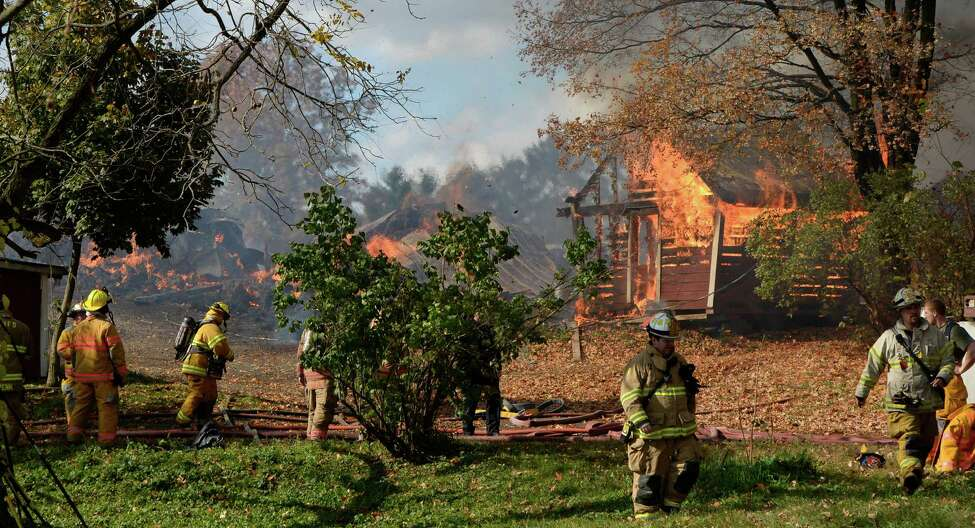Firefighters from Rensselaer and Columbia Counties fight a large blaze at the Peter Farm Friday afternoon, Oct. 18, 2013, in Castleton-on-Hudson, N.Y. Fire officials reported that as many as twenty young cows were lost in the fire. (Skip Dickstein/Times Union)