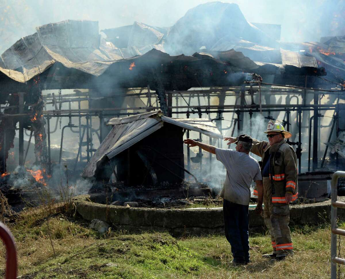 Farm owner Paul Peter, left speaks with Rensselaer County Deputy Fire Coordinator Bill Gummer at the Peter Farm Friday afternoon, Oct. 18, 2013, in Castleton-on-Hudson, N.Y. Fire officials reported that as many as twenty young cows were lost in the fire. (Skip Dickstein/Times Union)
