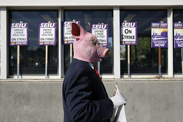 A man in a pig mask with a sign jokingly proclaiming he supports management walks past strike signs in Oakland. Photo: Michael Short, The Chronicle