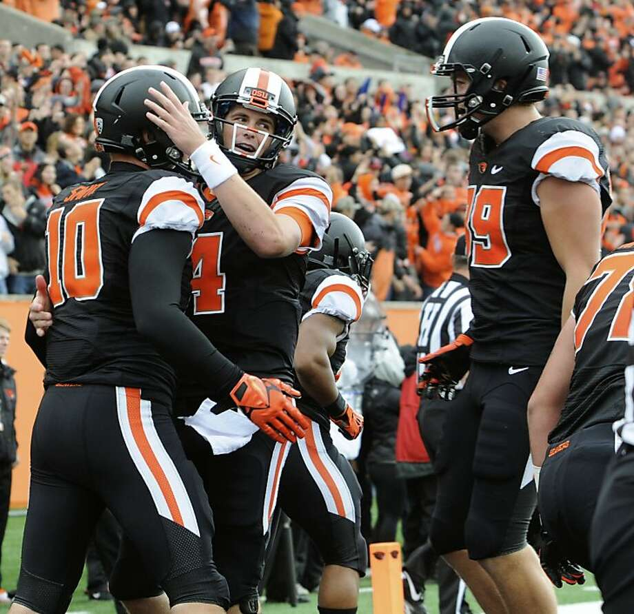 Oregon State's quarterback Sean Mannion (4) congratulates Caleb Smith (10) on his touchdown reception against Colorado in the first half of an NCAA college football game on Saturday, Sept 28, 2013, in Corvallis, Ore. (AP Photo/Greg Wahl-Stephens) Photo: Greg Wahl-Stephens, Associated Press