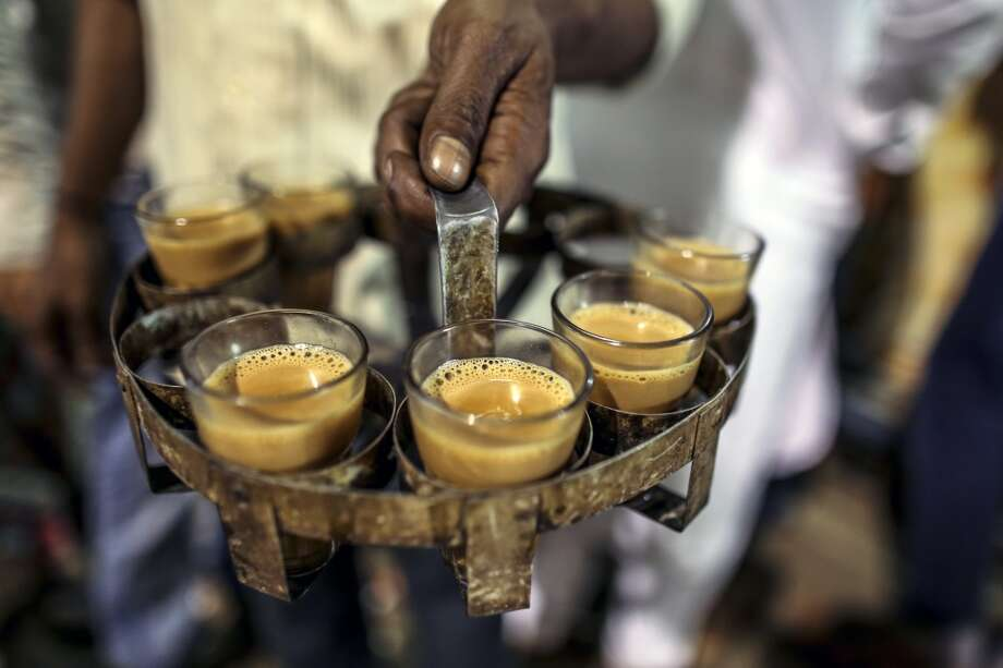 India: A man carries glasses of Indian spiced chai tea in Bangalore, India Photo: Dhiraj Singh, Bloomberg