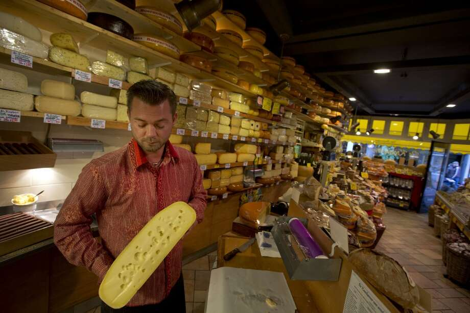 Netherlands: Maarten Huiskamp, left, prepares to cut a piece of Dutch cheese in De Kaaskamer store in Amsterdam, Netherlands. Photo: Peter Dejong, Associated Press