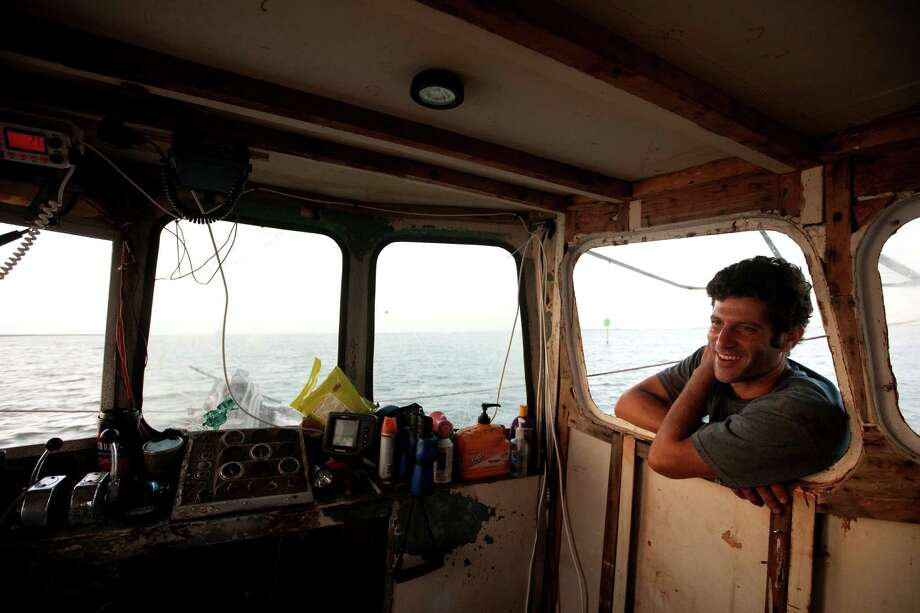 Eric Leshinsky with Discovery Shrimp & Oyster Company leans through a window to talk to friend Zach Moser, not pictured, while shrimping near the Houston Ship Channel, Friday, Sept. 27, 2013, in Kemah. The two artists bought a shrimp boat to shrimp the area for a better understanding of the Gulf Coast. The two plan to make art pieces from their observations. (Cody Duty / Houston Chronicle) Photo: Cody Duty, Staff / © 2013 Houston Chronicle
