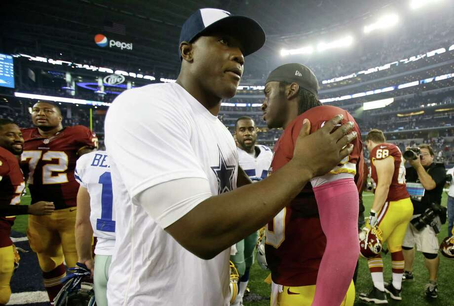 Dallas Cowboys' DeMarcus Ware, left, and Washington Redskins' Robert Griffin III, right, greet each other following an NFL football game, Sunday, Oct. 13, 2013, in Arlington, Texas. Ware left the game with an unknown left leg injury in the 31-16 Cowboys win. (AP Photo/Tim Sharp) Photo: Tim Sharp, Associated Press / FR62992 AP