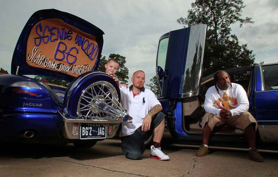"Junior Porter, 5, father B.G. Porter, who runs a customizing car shop and drives a 1999 Jaguar XK8 convertible, and Timothy ""Toolman"" Berard, who drives an old-school 1993 Cadillac, are part of the Blue Line car club.  ( Mayra Beltran / Houston Chronicle ) Photo: Mayra Beltran, Houston Chronicle / © 2013 Houston Chronicle"