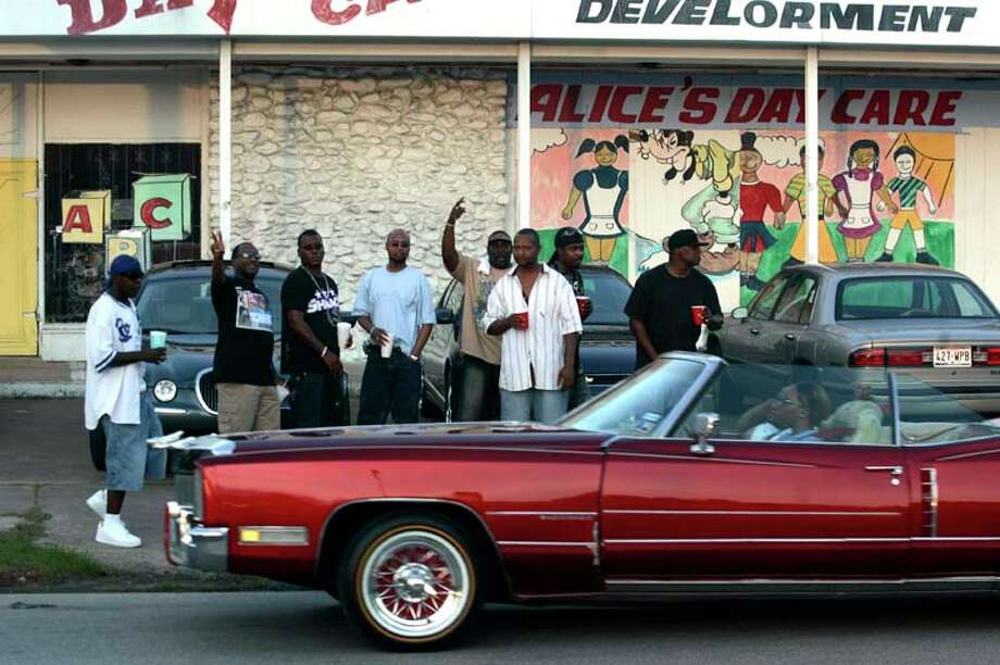 "A group watches the ""SLABs"" (Slow, Loud and Bangin' vehicles) drive down the 6800 block of Martin Luther King Blvd. in 2007. SLABs are customized cars with thick coats of paint, enlarged rims, expensive stereo systems, and video systems.Hundreds of people, hit the street every Sunday evening to watch the procession of cars and trucks with thousands of dollars of upgrades.( Johnny Hanson / For the Chronicle) Photo: Johnny Hanson, For The Chronicle / Freelance"