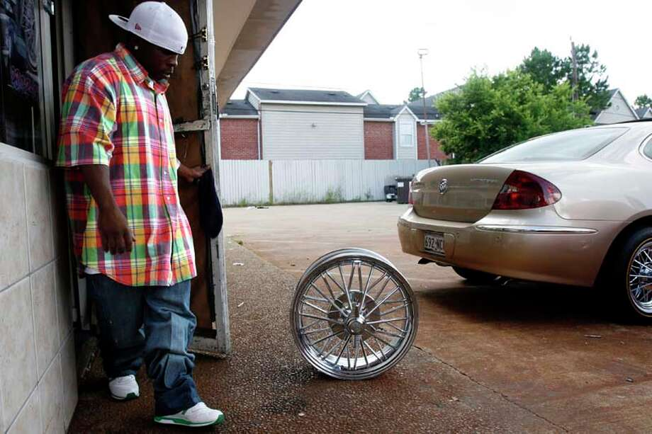 "SLAB owner, Rashaad Moore, looks at a 20-inch 1984 (""84s"") rim, the set of four valued at $4,500, at Da Slab Spot in 2007. The rims are one of the key elements in a SLAB. 