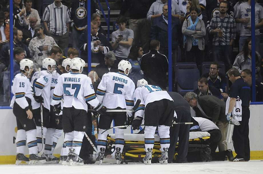 Sharks players surround Dan Boyle, who left on a stretcher after being driven into the boards. Photo: Bill Boyce, Associated Press