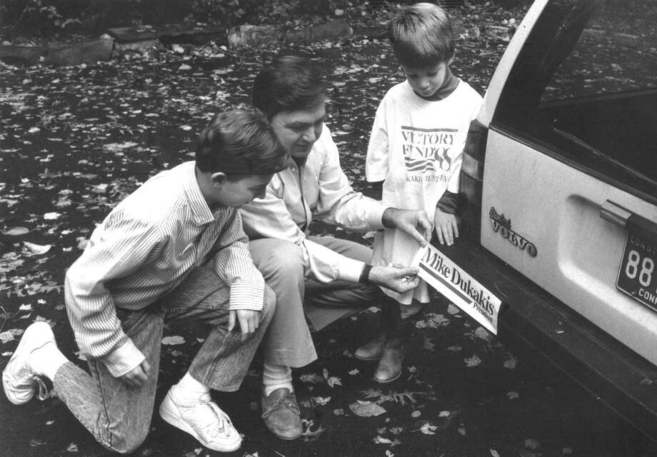 Stephen Fuzesi Jr., co-coordinator of the Mike Dukakis presidential campaign in Greenwich, puts a bumper sticker on his car, watched by his sons, 11-year-old Steve, left, and 6-year-old Tim, on Oct. 22, 1988. Photo: Greenwich Time, File Photo / Greenwich Time