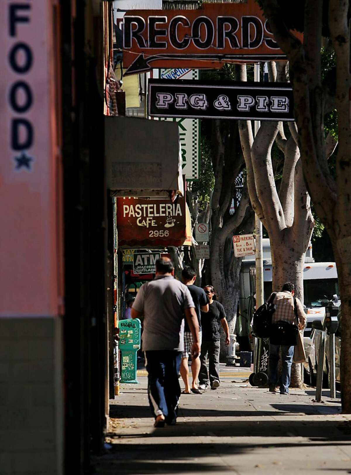 Pedestrians are seen beneath business signs as they walk on 24th st in San Francisco, Calif. on Friday, Oct. 18, 2013.
