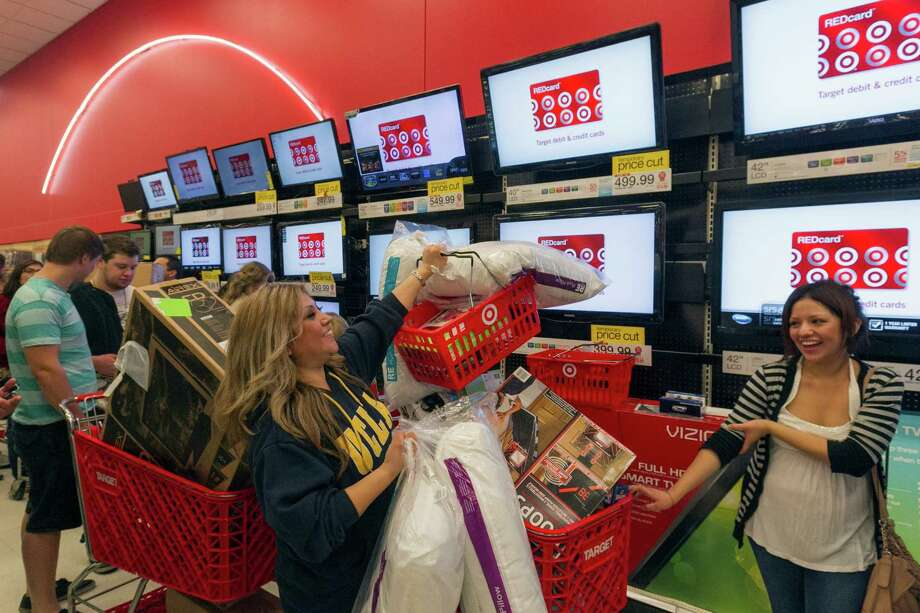 FILE - In this Nov. 22, 2012 file photo, Shopper Roxanna Garcia, middle, waits in line to pay for  her over a $1000.00 gifts at the Target store in Burbank, Calif.  Now that the U.S. has averted a default on its debt that could have sent the economy into a tailspin, it seems retailers avoided a train wreck heading into the holiday shopping season. Retailers hope that shoppers forget about the fact that the plan offers only a short reprieve until early next year long enough to open their pocketbooks. But they're fearful that consumers, facing a bombardment of news about continued political bickering,  could hunker down  until there's a permanent resolution. (AP Photo/Damian Dovarganes) ORG XMIT: NY118 Photo: Damian Dovarganes / AP
