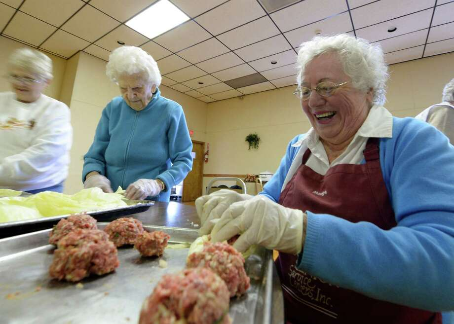 Madge Ten Eyck, right, prepares some of the 400 plus stuffed cabbages for the St. Basil's Russian Orthodox Church's Fall Harvest Fest Friday afternoon Oct. 18, 2013, in Watervliet, N.Y. The festival run Saturday from 10 til 3 p.m. (Skip Dickstein/Times Union) Photo: SKIP DICKSTEIN / 00024305A