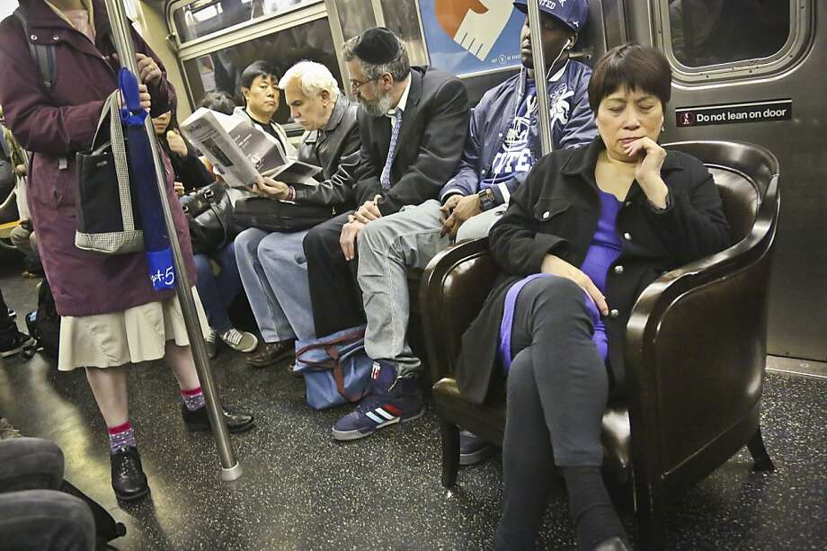 Jennifer Young, right, sits in a living room chair while riding the subway to her home in Brooklyn, N.Y., on Thursday, April 18, 2013.  Photo: Bebeto Matthews, Associated Press