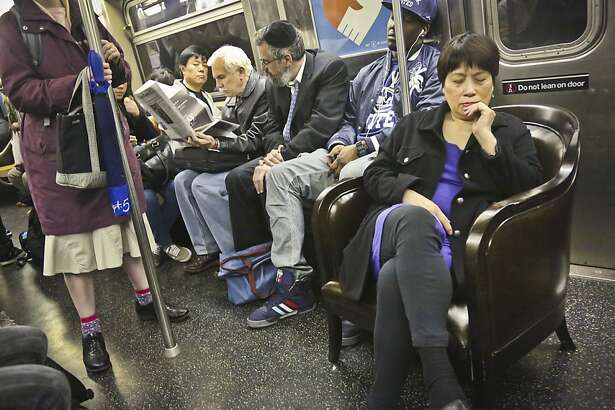 "Jennifer Young, right, sits in a living room chair while riding the subway to her home in Brooklyn, N.Y., on Thursday, April 18, 2013.  ""She's riding first class,"" said fellow passenger Cecil Campbell, ""you just need a glass of wine now,"" he added.  Young, who bought the chair at a Manhattan store, join many New Yorkers who take advantage of the efficiency of city subway-- part of ""North America's largest public transit system,"" according to the MTA, to move large appliances and furniture for the cost of a subway ride."