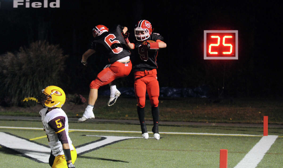 New Canaan's Teddy Bossidy and Cole Turpin, right, celebrate Turpin's touchdown as the New Canaan High School Rams hosts the Chicopee High Pacers in a football game in New Canaan, Conn., Oct. 18, 2013.