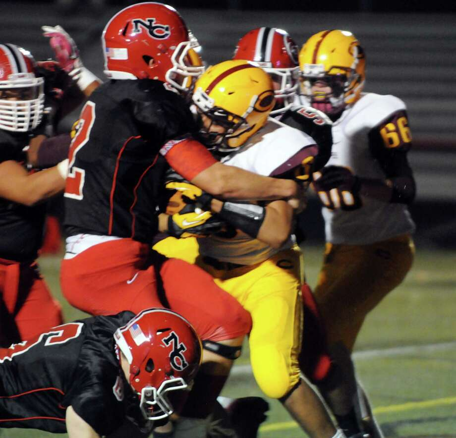 New Canaan's Cole Harris collides with Chicopee's Isaiah Green as the New Canaan High School Rams hosts the Chicopee High Pacers in a football game in New Canaan, Conn., Oct. 18, 2013. Photo: Keelin Daly / Stamford Advocate Freelance