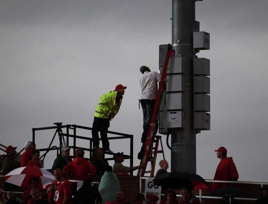 Workers attempt to repair the stadium lights prior to the Katy Seven Lakes high school football game cancellation due to a lighting problem at Rhodes Stadium Friday, Oct. 18, 2013, in Katy. Photo: James Nielsen, Houston Chronicle / © 2013  Houston Chronicle
