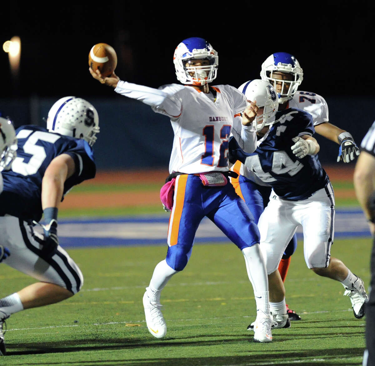 Danbury quarterback Anferny Ith (# 12) throws a first quarter touchdown pass while being pressured by Staples defenders Ian Burns (# 55), at left, and Austin Nicklas (# 44), at right, during the high school football game between Staples High School and Danbury High School at Staples in Westport, Friday, Oct. 18, 2013.