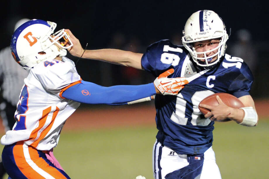 At left, Staples quarterback Jack Massie (# 16) stiff-arms  Danbury's Eric Henry (# 42) on a running play during the high school football game between Staples High School and Danbury High School at Staples in Westport, Friday, Oct. 18, 2013. Photo: Bob Luckey / Greenwich Time