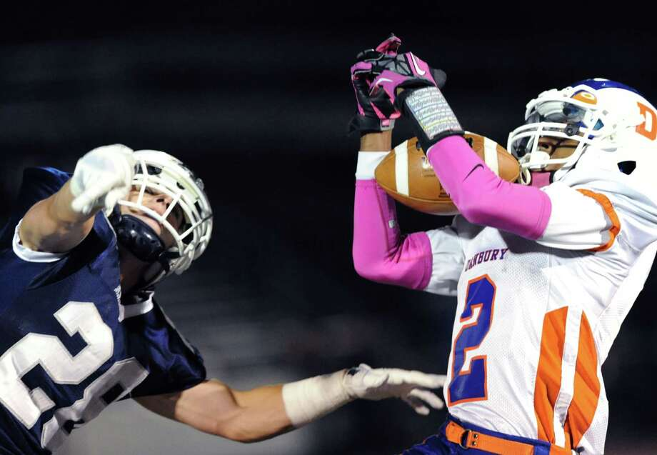 A leaping Staples defender, Jack Greenwald (# 28), misses the deflection as Elijah Duffy (# 2) of Danbury, at right, makes a catch that he ran in for a first quarter touchdown during the high school football game between Staples High School and Danbury High School at Staples in Westport, Friday, Oct. 18, 2013. Photo: Bob Luckey / Greenwich Time