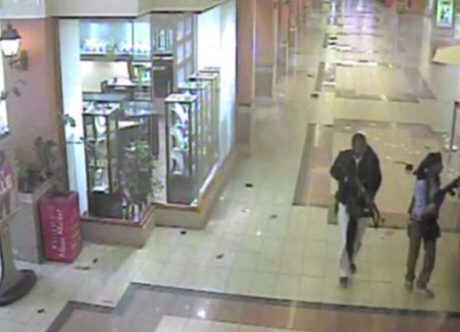 In this frame grab from surveillance video provided by Kenya Police via KTN, two gunmen wander through the Westgate Mall, Sept. 21, 2013, in Nairobi, Kenya. Several attackers from the Somali militant group al-Shabab stormed the mall on Sept. 21, killing at least 67 people during a four-day siege. (AP Photo/Kenya Police via KTN) ORG XMIT: NY132 Photo: Uncredited / Kenya Police via KTN