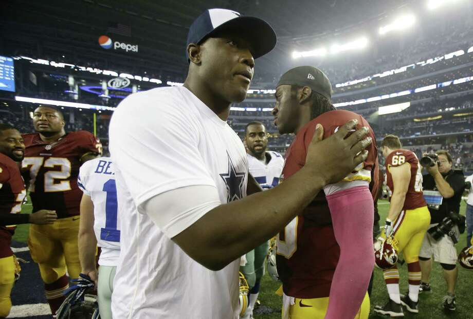 Defensive end DeMarcus Ware (left), greeting Robert Griffin III after Dallas beat Washington, likely will miss the first game of his career with a quad injury. He has played in 134 straight. Photo: Tim Sharp / Associated Press