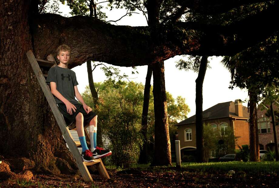 Justin Davis, 12, can no longer climb trees after the onset of Giant Axonal Neuropathy, a rare, nerve-debilitating genetic disease. Photo: Cody Duty, Staff / © 2013 Houston Chronicle