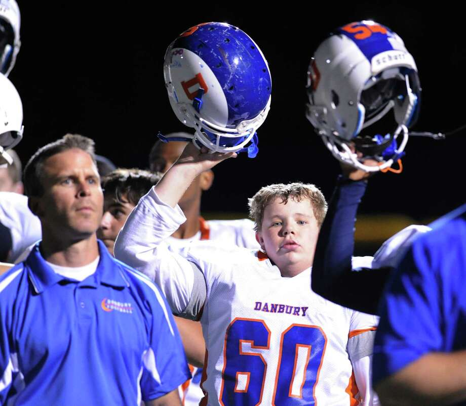 Danbury's Quentin Falkowski (# 60) raises his helmet at the start of  the high school football game between Staples High School and Danbury High School at Staples in Westport, Friday, Oct. 18, 2013. Photo: Bob Luckey / Greenwich Time