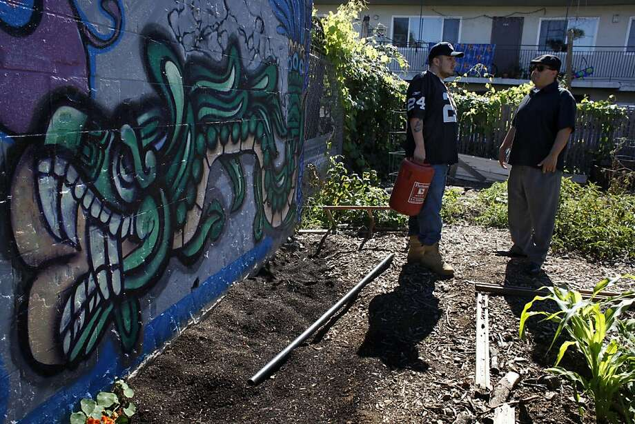 Ruben Leal (left) and George Galvis survey a Community Garden plot. Pending legislation would make more land in Oakland available for food. Photo: Lacy Atkins, The Chronicle