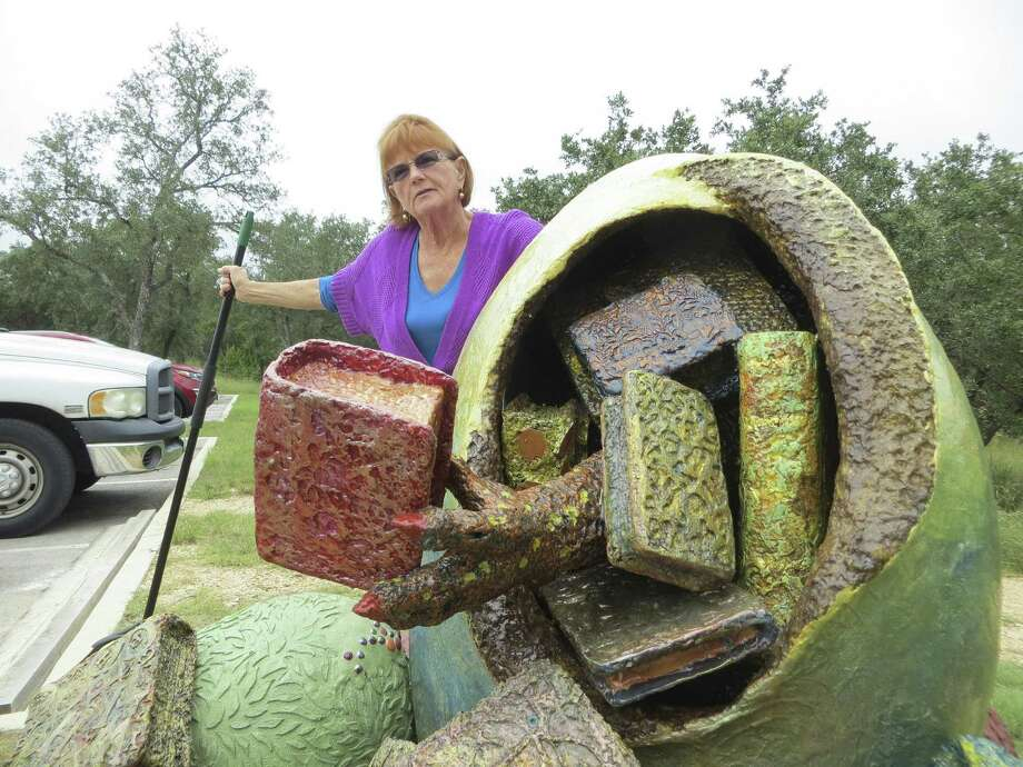 "Artist Sherry Gansle cleans up around ""Thesaurus,"" her dinosaur egg sculpture, outside the Tye Preston Memorial Library in Canyon Lake. Its unveiling is Saturday. Photo: Zeke MacCormack / San Antonio Express-News"