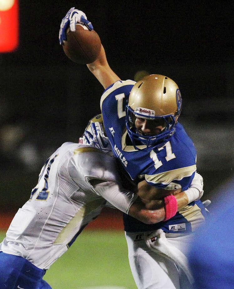 Alamo Heights' Noah Hernandez (17) tries to escape a tackle by Kerrville Tivy's Josh Appel (21) Orem Stadium on Friday, Oct. 18, 2013. Photo: Kin Man Hui, San Antonio Express-News / ©2013 San Antonio Express-News