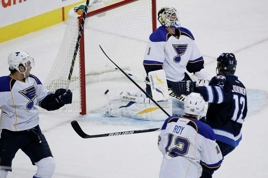 Winnipeg Jets' Olli Jokinen (12) scores on St. Louis Blues goaltender Brian Elliot during the first period of an NHL hockey game, Friday, Oct. 18, 2013 in Winnipeg, Manitoba.  (AP Photo/The Canadian Press, John Woods) ORG XMIT: JGW103 Photo: John Woods / The Canadian Press