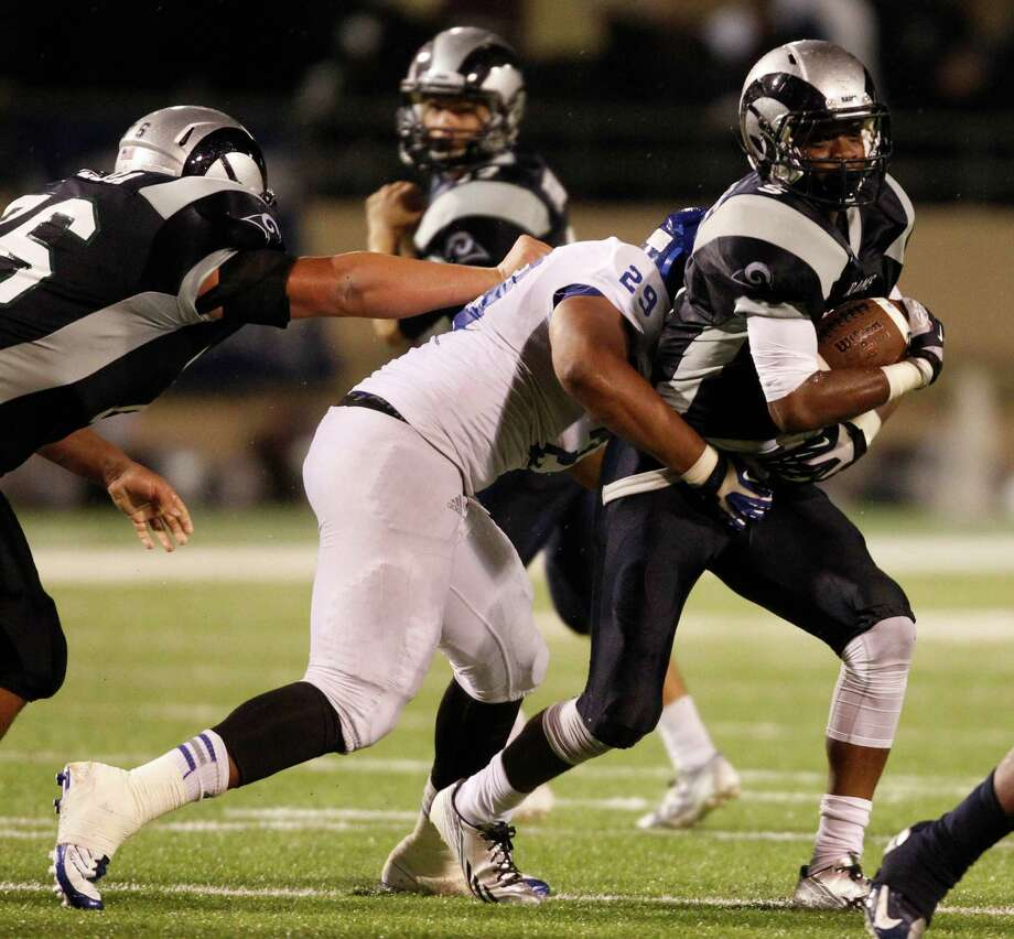 Cy-Ridge's Anthiony Williams (5) is tackled for a loss by Cy-Creek's Joe Ellis during the first half of a high school football game, Friday, October 18, 2013 at Pridgeon Stadium in Houston. Photo: Eric Christian Smith, For The Chronicle