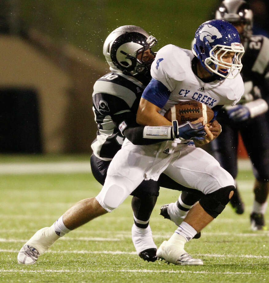 Cy-Creek's Jacob Korte (4) is tackled by Cy-Ridge's Clarence Roberson during the first half of a high school football game, Friday, October 18, 2013 at Pridgeon Stadium in Houston. Photo: Eric Christian Smith, For The Chronicle